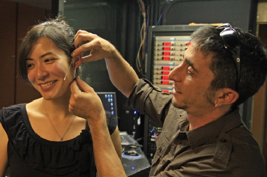 Alan Ceccarelli placing an E6 Omni Earset microphone on a student.